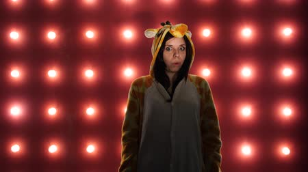 éretlen : Female is shocked or surprised. Woman in a bright childrens pajamas in the form of a kangaroo. emotional portrait of a student. costume presentation of childrens animator.