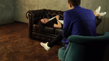 mladé ženy : Young woman answering questions of faceless man. Young confused woman sitting on leather couch and talking with unrecognizable confident man in suit