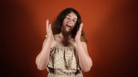astonishment : Shocked astonished pretty young woman touching her face in orange background Stock Footage