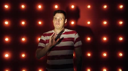 sem camisa : A man in a striped t-shirt on a red background. Looking camera says no Stock Footage