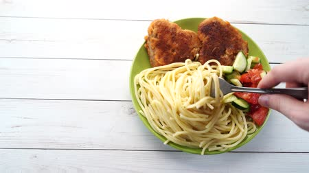 chicken recipes : traditional dish consisting of spaghetti with chicken cutlets and vegetable salad. Stock Footage