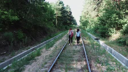 Two women are on the railway going into the distance, surrounded by green trees. Girls walk in the woods