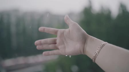 Rainy weather, rain drops falling on womans hand. Rain is dropping on a mans hand.