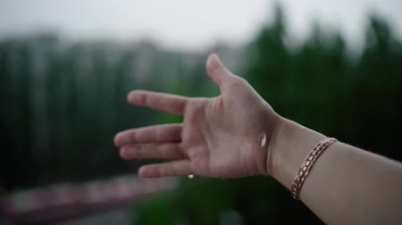 Close up of woman putting her hand in the rain catching drops of rain, water Concept. 動画素材