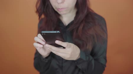 Young woman holding mobile phone in hand on orange background. Female typing a message on a smartphone