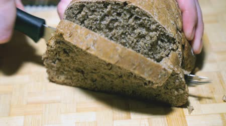 charakteristický : Rye-wheat bread is cut with a knife on a board Dostupné videozáznamy