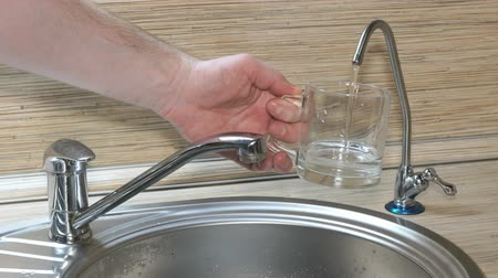 necessity : Hand is pouring a glass of drinking water from the filter