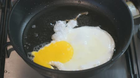scrambled eggs : Frying eggs in a skillet. Skillet stands on the hob. Closeup Stock Footage