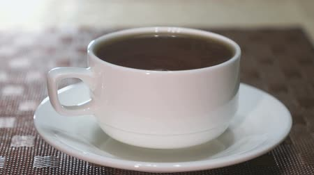káva : Porcelain mug with black tea is on the table. Steam coming from a mug