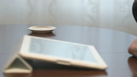 КПК : Woman works over documents using a digital tablet and drinks coffee