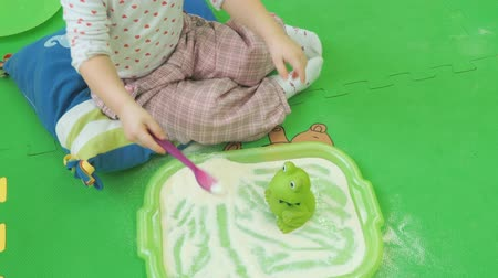 búzadara : Child sits on floor and plays with a toy