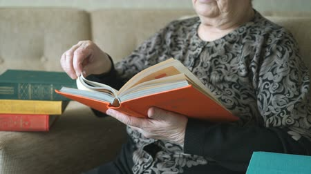 növelni : Old grandmother reading the book on the couch