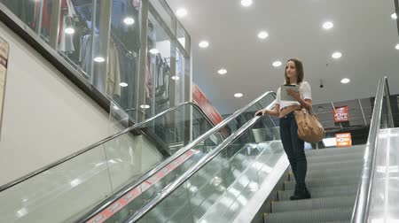 adresář : Stylish fashionable girl rides on an escalator