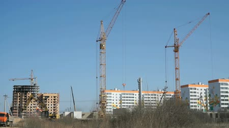 montáž : Construction cranes work at construction site