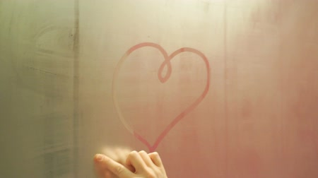 self perception : Hand draws a heart on a foggy mirror