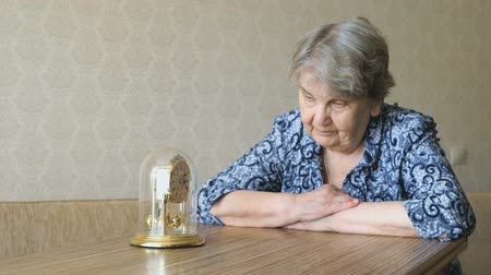 szomorúság : Old woman looks at the table clock with pendulum