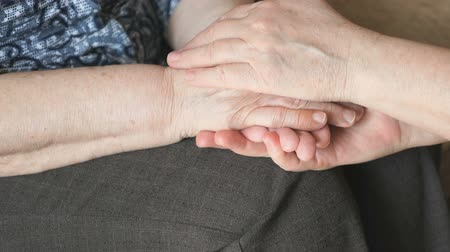 segít : Woman strokes an old wrinkled womans hand