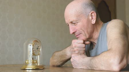 imaginar : Mature man looks at the table clock with pendulum Stock Footage