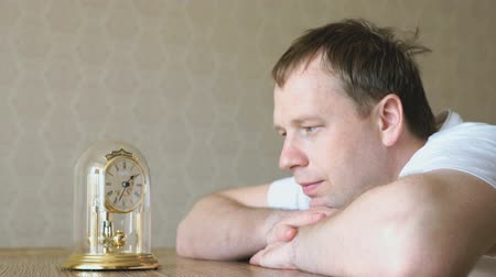 sentiment : Serious man looks at the table clock with pendulum Stock Footage