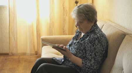devise : Old woman looks at pictures using a digital tablet Stock Footage
