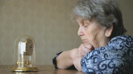 sentiment : Old woman looks at the table clock with pendulum