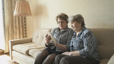 devise : The old woman and her friend looking at pictures