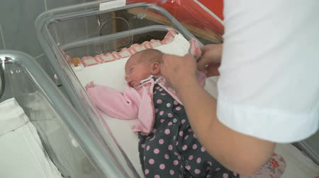 medicals : Nurse swaddles newborn infant in medical chamber