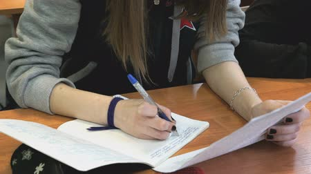 yazarak : The girl sitting at the school desk writes the text in a notebook indoors