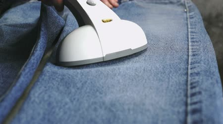 crinkle : Woman steaming the denim fabric on the ironing table indoors. Close up Stock Footage