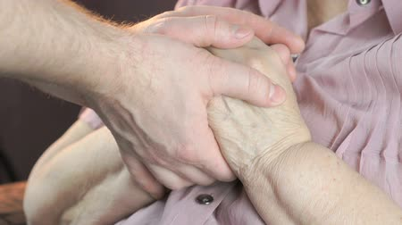 stary : Man holding the old wrinkled hands of elderly woman. Man soothes the elderly woman during stress. Close up