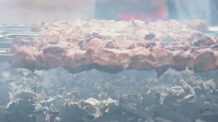 etli : Cooking of pig meat on the metal skewers on coals outdoors. Close up