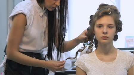 anelzinho : Professional barber makes hairstyle for the young girl at the beauty saloon. Making of hairstyle volume