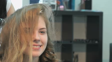 anelzinho : Professional stylist makes the curls to an attractive brown-haired using a hot curling Stock Footage