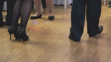 luxúria : Women and men dancing at a wedding indoors. Peoples feet close up