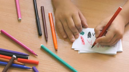 favori : Child sitting at the desk draws the picture on the paper sheet using the colored felt pens. Close-up