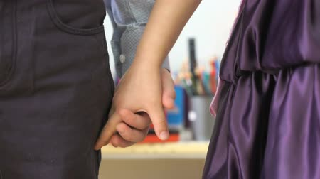 kezek : Little boy and girl standing each other holding hands at the kindergarten. Close up