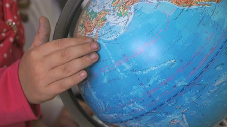 çevirmek : Child twists around the axis model of globe of world. Close-up