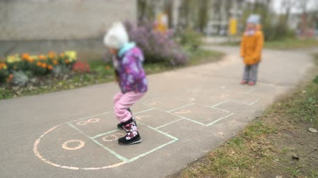 dehet : Two little girls playing hopscotch outdoors