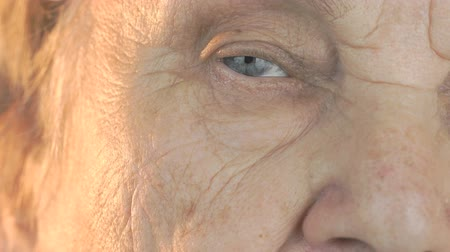 starość : Elderly woman opening and closing eyes. Close up