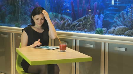 külotlu çorap : Attractive brunette girl aged 20s sitting at a cafe drinking juice and watching photos using a silver computer tablet Stok Video