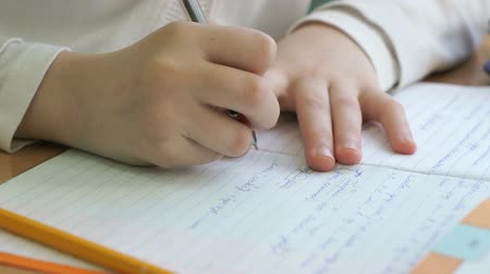 решить : Child writes the text in the workbook with the ball point pen at school