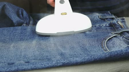 crinkle : The process of steaming of the jeans using the professional steam cleaner. Close up Stock Footage
