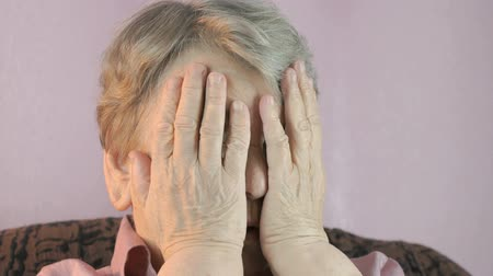 frustração : The old woman sitting indoors covers face her hands Stock Footage