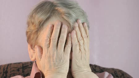alarmed : Adult woman sitting indoors covers face her hands Stock Footage