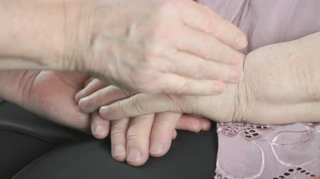 бабушка : Woman strokes the old wrinkled womans hands during a difficult illness. Close up