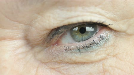 crinkle : Adult woman aged 60s blinking one eye. Close up
