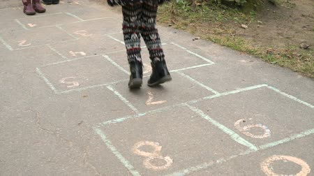 dehet : Legs of little girl jumping on the asphalt. Child playing the hopscotch outdoors. Close-up