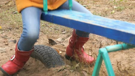 gerekçesiyle : Small girl in jeans, red boots and yellow jacket riding on swing at playground
