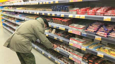 bakkal : VELIKIY NOVGOROD, RUSSIA - JANUARY 10, 2017: Elderly man aged 70s chooses bread at Lenta supermarket