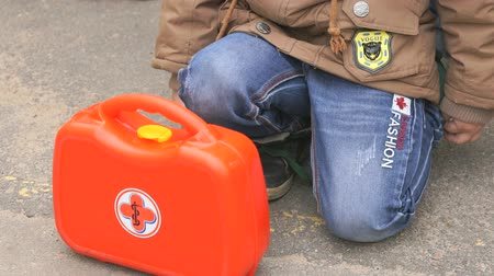 haunches : MOSCOW, RUSSIA - OCTOBER 6, 2017: Child sit on his haunches near orange first aid kit outdoors